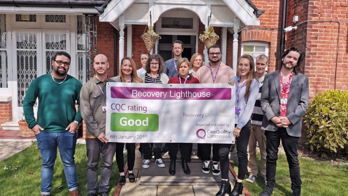 recovery lighthouse team holding cqc result banner